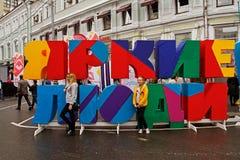 Folk som står nära ställning med `en för folk för inskrift` den ljusa på `en för folk för festival` den ljusa på stadsdag på Negl Royaltyfri Bild