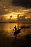 Folk som står och ror på solnedgången Arkivfoto