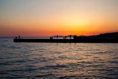 Folk som står på pir i solnedgång Royaltyfri Bild