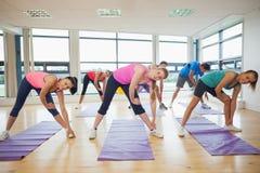 Folk som sträcker händer på yogagrupp i konditionstudio Arkivbilder