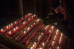Folk som tänder stearinljus i den Notre Dame domkyrkan i Paris, Frankrike Att bränna en stearinljus är en vanlig övning i katolic Arkivbild