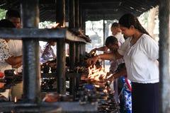 Folk som tänder stearinljus utanför templet av tandreliken fotografering för bildbyråer