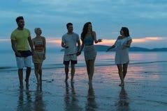 Folk som talar på stranden på solnedgången, ung turist- grupp som går på havet i aftonkommunikation royaltyfri foto