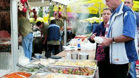 Folk som tar disk på gatamatfestival, skadliga stekte potatisar, lagade mat peppar, mässa lager videofilmer