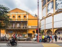 Folk som tillbaka korsar gatan över Grecian-spanjor stilbyggnader fotografering för bildbyråer