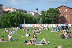 Folk som tycker om avslappnande det fria på gräsmattan Arkivfoto