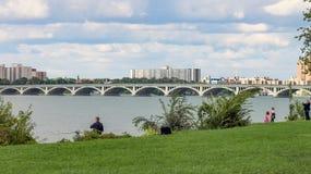 Folk som tycker om det fria på Belle Isle med den iconic MacArthur bron i bakgrunden royaltyfri foto