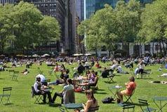 Folk som tycker om en trevlig dag i Bryant Park Arkivbilder