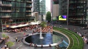 Folk som tycker om restauranger och service runt om en springbrunn på Potsdamerplatz Sony Center stock video