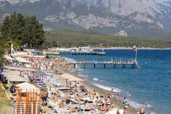 Folk som tycker om solen och havet på det turkoshavet och Pebblet Beach Kemer Turkiet Fotografering för Bildbyråer