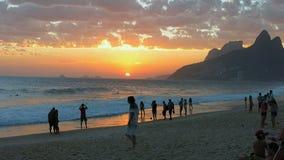 Folk som tycker om solnedgången på den Ipanema stranden, Rio de Janeiro lager videofilmer