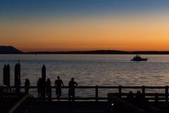 Folk som tycker om solnedgången på pir av havet royaltyfri fotografi