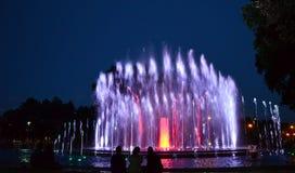 Folk som undrar den färgglade springbrunnen Royaltyfri Bild
