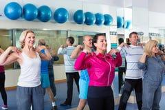 Folk som utbildar i en idrottshall som gör pilates Royaltyfria Bilder