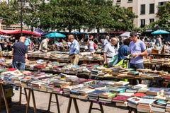 Folk som väljer använda böcker på den loppaAligre marknaden Paris Fra Arkivbilder