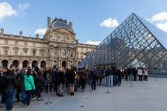 Folk som väntar i lång kö på Louvremuseet i Paris Frankrike Royaltyfri Bild