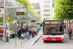 Folk som väntar på bussen på hållplatsen i Friedensplatz Arkivfoton
