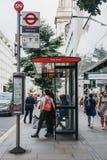 Folk som väntar på en buss på brödgatahållplatsen i staden av London, UK arkivfoto