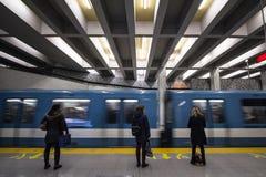 Folk som väntar på en gångtunnel i den Berri-UQAM stationsplattformen, grön linje, medan ett tunnelbanadrev kommer, med en hastig royaltyfria bilder