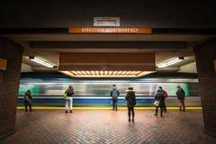 Folk som väntar på en gångtunnel i den Snowdon stationsplattformen, orange linje, medan ett tunnelbanadrev kommer, med en hastigh arkivbilder