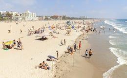 Folk som vilar på stranden under högsäsong Arkivbilder