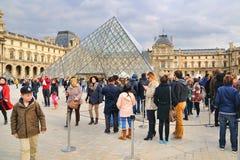 Folk som väntar, genom att använda en kö, för att besöka Louvre Royaltyfri Bild