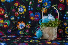 Folk style easter decoration with white and blue eggs on painted textile background. royalty free stock photography