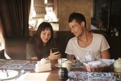 Folk, teknologi, livsstil och datummärkningbegrepp - lyckligt par med smartphonen som dricker kaffe och smoothien på kafét arkivfoton
