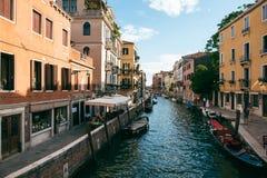 Folk tillsammans med en kanal i Venedig på en solig sommardag arkivbild