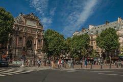 Folk, träd och byggnader på hörnet av en gata i Paris arkivfoto