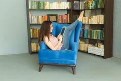 Folk, utbildning och teknologibegrepp - kvinna som läser den digitala minnestavlan i fåtölj i arkiv royaltyfri bild