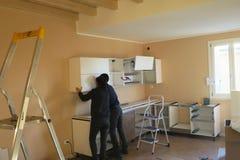 Folkarbetare som försöker att installera ett kök royaltyfri foto