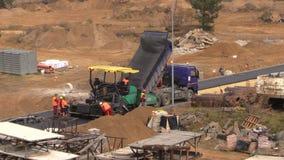Folkarbete med asfalttrottoarmaskiner i konstruktionsplats arkivfilmer