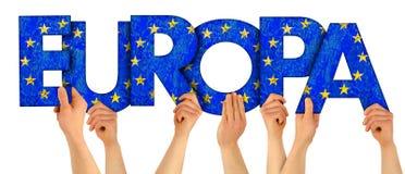 Folkarmhänder som upp rymmer träbokstavsbokstäver som bildar den tyska ordEuropaenglish översättningen: Europa i europeisk union arkivbild