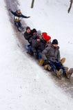 Folkbarn rider på vintersnön som sledding från kullar Vinter som spelar, gyckel, snö Royaltyfri Bild