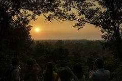 Folket är Concentratedly som tar solnedgångbilden Arkivbilder