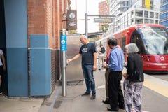 Folket är i linjen som ska knackas lätt på på opalkort för att få i en spårvagn på hö Arkivfoton