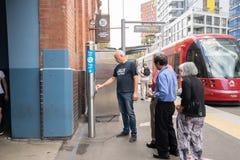 Folket är i linjen som ska knackas lätt på på opalkort för att få i en spårvagn på Hay Marke Royaltyfria Foton