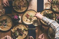 Folket äter sunda mål och den festliga tabellen för drinkalkohol arkivbild