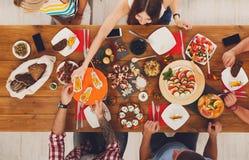 Folket äter sunda mål på det festliga tabellmatställepartiet royaltyfri foto