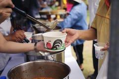 Folket överstiger för att donera mat från volontärer: Matbegrepp av hopp: Fri mat för fattigt och hemlöst folk donerar mat till royaltyfri foto