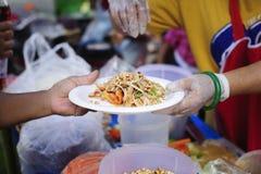 Folket överstiger för att donera mat från volontärer: Matbegrepp av hopp: Fri mat för fattigt och hemlöst folk donerar mat till arkivbilder