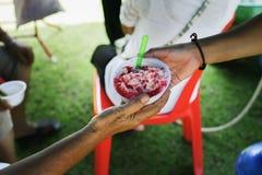 Folket överstiger för att donera mat från volontärer: Matbegrepp av hopp: Fri mat för fattigt och hemlöst folk donerar mat till royaltyfria foton