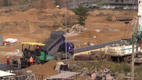 Folket arbetar med förberedande maskiner för asfalt i konstruktionsplats stock video
