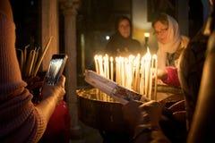 Folket ber i kyrka och sätter stearinljus royaltyfria foton