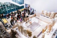 Folket besöker museet som byggdes på plats av den forntida romerska templet i den forntida staden Narona Arkivbild