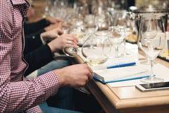 Folket betraktar färgen av vinet och försöket hur det luktar i olika exponeringsglas Man som gör anmärkningar Arkivbilder