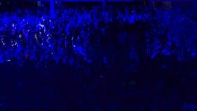 Folket dansar på en konsert i ljuset av en blå strålkastare stock video