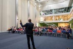 Folket deltar i den Digital marknadsföringskonferensen i stor korridor Arkivbilder