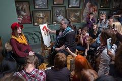 Folket deltar i det fria seminariet under den öppna dagen i vattenfärgskola Arkivfoton